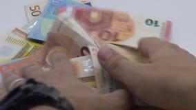 La cámara lenta de la mano saca las cuentas de los euros de diversos valores Dinero que gana metrajes
