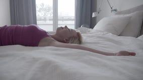 La cámara lenta de la mujer feliz que salta y acuéstese en su cama en casa, perfil
