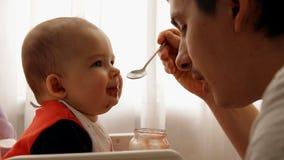 La cámara lenta de un padre feliz joven alimenta su puré de la fruta del bebé del hijo metrajes