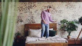La cámara lenta del individuo barbudo hermoso tiene el baile de salto de la diversión en cama y escuchar la música en auriculares metrajes
