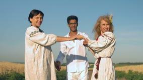 La cámara lenta, dos mujeres en trajes nacionales y un hombre indio en gafas se aferran a las manos y al soporte de la sonrisa en metrajes