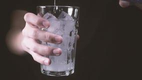 La cámara lenta el adolescente celebra un vidrio con hielo y vierte el agua almacen de video