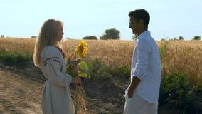 La cámara lenta, el hombre indio en vidrios y la camisa blanca comunican con la mujer hermosa en ropa nacional y almacen de metraje de vídeo