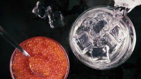 La cámara lenta en un vidrio de hielo y la vodka vierten soda en la tabla con la opinión superior del caviar almacen de metraje de vídeo