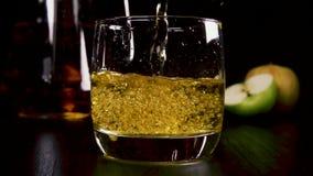 La cámara lenta en una bebida alcohólica fuerte en un vidrio vierte el jugo almacen de video