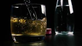 La cámara lenta en una bebida alcohólica fuerte en un vidrio vierte soda almacen de metraje de vídeo