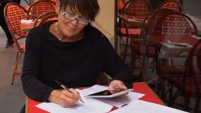 La cámara lenta envejeció la tableta del uso de la mujer de negocios para escribir la declaración de las finanzas almacen de metraje de vídeo