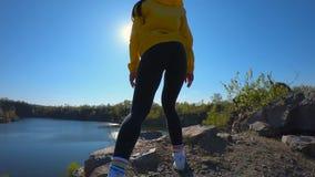 La cámara lenta estupenda de la mujer del caminante que va al top de la montaña, disfruta y aumenta de las manos