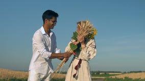 La cámara lenta, hombre indio en pedazos da a mujer adulta al manojo de brotes y de girasol del trigo al lado de campo de trigo almacen de metraje de vídeo