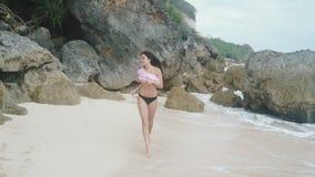 La cámara lenta, muchacha en un traje de baño corre a lo largo de la playa con la arena blanca y las ondas grandes, las rocas her almacen de video