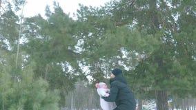 La cámara lenta, papá lanza a su hija hasta el cielo en el bosque del invierno almacen de metraje de vídeo