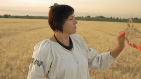 La cámara lenta, primer, mujer en camisa nacional se coloca en el campo y mira puntos del trigo en la mano ligada por el rojo almacen de video