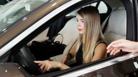 La cámara lenta tiró de la mujer que se sentaba en coche en el centro, comprando el automóvil almacen de video