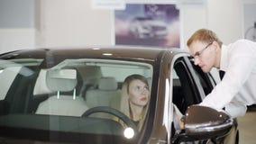La cámara lenta tiró de la mujer que se sentaba en la rueda del coche en el centro almacen de metraje de vídeo