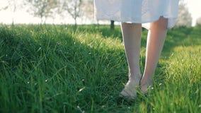 La cámara lenta tiró de los pies desnudos de la chica joven que caminaban y que corrían en hierba verde metrajes