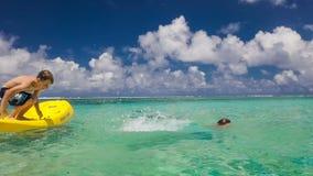 La cámara lenta tiró del salto de dos muchachos de la canoa al océano tropical almacen de video