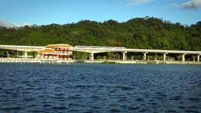 La cámara lenta un tren elevado viaja en el bridt sobre un lago en el parque almacen de metraje de vídeo