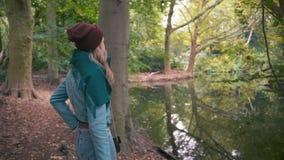 La cámara lenta una muchacha desconocida joven de la mujer en un sombrero rojo y una chaqueta azul, en la caída en un parque cerc almacen de video