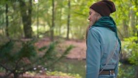 La cámara lenta una mujer joven, una muchacha en un sombrero rojo y chaqueta azul, en el parque invita para ir con ella Sonríe y  metrajes