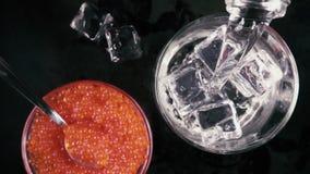 La cámara lenta vierte la vodka en el vidrio con hielo en la tabla con la opinión superior del caviar almacen de metraje de vídeo