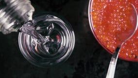 La cámara lenta vierte la vodka en un vidrio en la tabla con la opinión superior del caviar almacen de video
