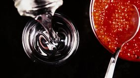La cámara lenta vierte la vodka en un vidrio en una tabla negra con la opinión superior del caviar rojo almacen de video