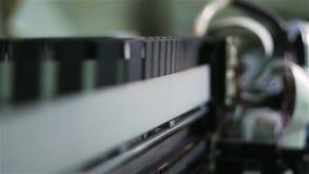 La cámara macra se mueve a lo largo de fabricante del cartel con la cabeza de impresión almacen de metraje de vídeo