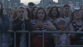 La cámara muestra los fan de música que aplauden y que gritan en el concierto almacen de video
