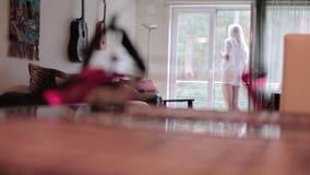 La cámara muestra que helicóptero del juguete en funcionamientos del escritorio y del blonde al balcón después agita la mano almacen de metraje de vídeo