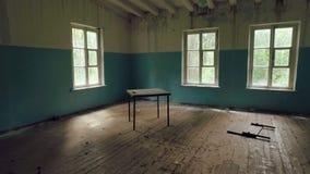 La cámara mueve la casa arruinada interior, los muebles rotos y la basura, luz de ventanas, sitio vacío metrajes
