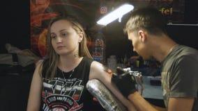 La cámara pasa el artista Making Picture del tatuaje en el brazo de la muchacha