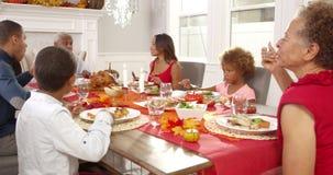 La cámara rastrea para mostrar a la familia extensa que se sienta alrededor de la tabla para la comida de la acción de gracias almacen de metraje de vídeo