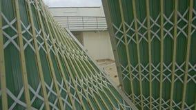 La cámara se acerca a la entrada del edificio con la cerca caida
