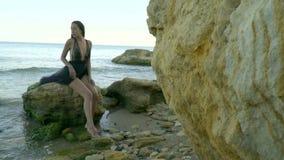 La cámara se acerca a una muchacha triste en un vestido negro del aire que se siente en una roca en una playa de piedra en el med metrajes