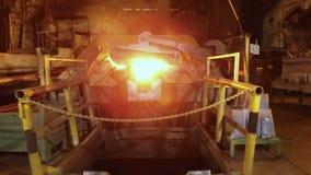 La cámara se está moviendo adelante al horno, en la fundición en planta metalúrgica, taller oscuro y aluminio candente almacen de metraje de vídeo