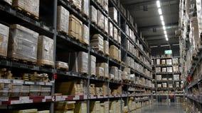 La cámara se levanta en estantes de las cajas de cartón dentro de un almacén de almacenamiento metrajes