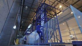 La cámara se mueve al trabajador que sube para arriba la escalera a la plataforma especial metrajes