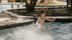 La cámara se mueve alrededor del pequeño muchacho caucásico de 4-6 años feliz que se divierte en una piscina soleada del verano q almacen de metraje de vídeo
