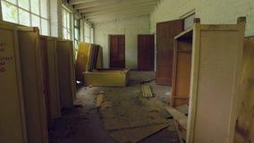 La cámara se mueve dentro del edificio abandonado y devastado viejo, muebles rotos, basura almacen de video