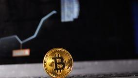 La cámara se mueve desde gráfico del crecimiento en monitor al modelo de Bitcoin almacen de metraje de vídeo