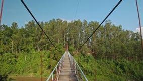 La cámara se mueve a lo largo de puente colgante sobre el río en parque