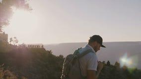 La cámara sigue al hombre turístico joven activo feliz que camina con la mochila, mirando el paisaje épico de la puesta del sol d almacen de video