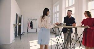 La cámara sigue al subdirector de sexo femenino joven hermoso que habla con los hombres de negocios multiétnicos en oficina cómod almacen de metraje de vídeo
