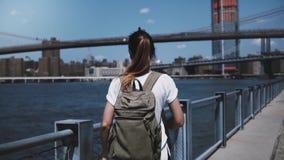 La cámara sigue al turista femenino joven con la mochila que disfruta de caminar relajado hacia el puente de Brooklyn en la orill almacen de metraje de vídeo
