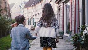 La cámara sigue el paseo de dos niños que lleva a cabo las manos opinión de la parte posterior de la cámara lenta La muchacha y e metrajes