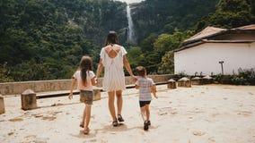 La cámara sigue a la madre joven feliz con dos niños que caminan hacia la opinión de la cascada de la selva que sorprende en la c metrajes