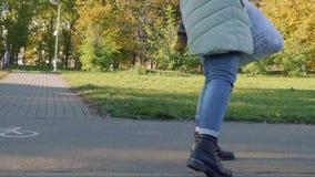 La cámara sigue a la mamá con el pequeño hijo en manos en parques del otoño el día soleado Visión posterior almacen de video