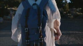 La cámara sigue a la mujer joven feliz con la mochila que camina a lo largo de la carretera de asfalto de la puesta del sol del v metrajes