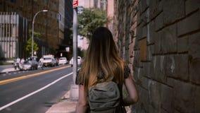 La cámara sigue a la mujer morena europea con el pelo largo del vuelo que camina a lo largo de la pared grande del edificio de la almacen de video