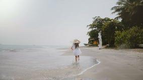La cámara sigue a la pequeña muchacha de 5-7 años hermosa feliz en el sombrero de paja grande que corre a lo largo de la playa tr almacen de metraje de vídeo